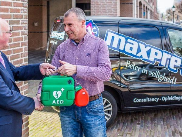 Hoe werkt een AED - AED wordt overhandigd aan burgemeester
